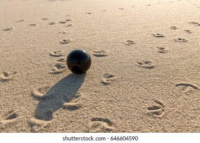 Black glass ball on the sandy beach