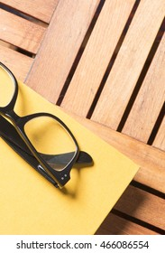 Black glasses and colorful notebook lying on wooden table. Lifestyle image. Concept of education, work and reading.