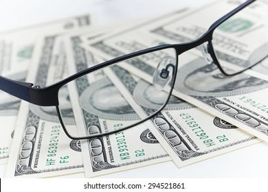 Black glasses lie on the American dollars