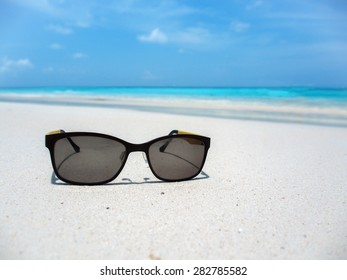 black glasses on the beach with shallow depth of field