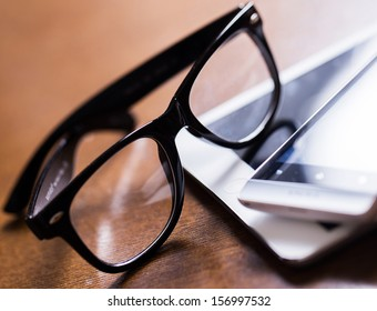 Black glasses and a white tablet on a wooden table