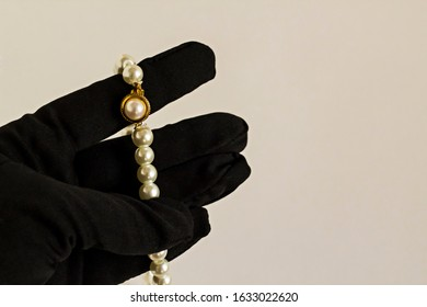 Black gloved hand holding pearl necklace on white surface.