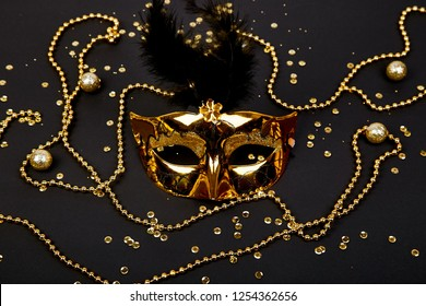 Black and gold carnival mask. Top view image of masquerade background. Flat lay. Mardi Gras celebration concept. Copy space.