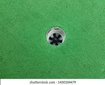 black golf ball in hole on miniature golf course
