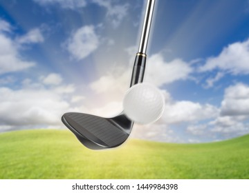 Black Golf Club Wedge Iron Hitting Golf Ball Against Grass and Blue Sky Background.