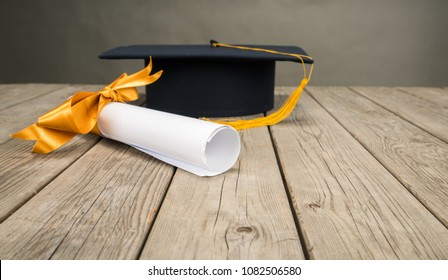 Black Graduation Cap with Degree, diploma with yellow ribbon Isolated on wooden Background in retro style.