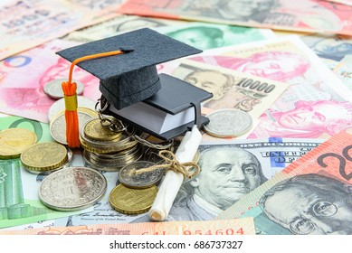 Black graduation cap / hat, a rolled up scroll diploma / certificate and a tiny or small book on pile of coin and banknotes. Concept of international graduate program or graduate study abroad program.