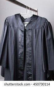 Black graduation gowns hanging on cloth hangers on wooden rail