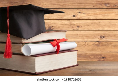 Black graduation hat with diploma and book