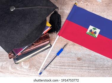 Black graduation hat on books next to Haiti flag, education concept, top view