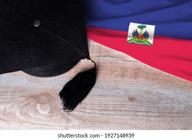 Black graduation hat on Haiti flag, education concept, top view