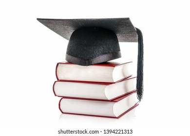 Black graduation hat on pile of three hard cover books over white