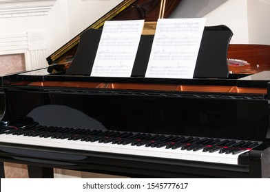 Black grand piano with top open and keys reflected on the inside of the cover