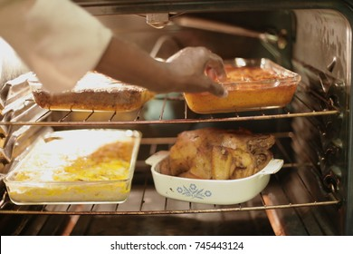 Black grandmother cooking Thanksgiving soul food dinner with love. Mac and Cheese, candied yams, and chicken in the over ready to celebrate with the family