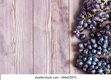 Black grape branch on dark wooden background. Berry fruit botanic plant. Eating healthy food. Copy space for text top view
