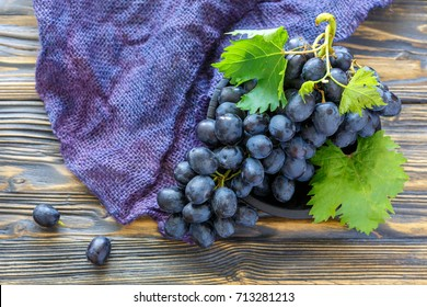Black grapes in a bowl on old wooden table with burlap.