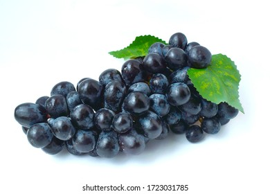 Black grapes, large fresh fruits with green leaves on a white background