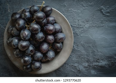 Black grapes on pewter dish with grey background