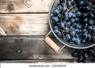 Black grapes in a saucepan. On a wooden background.