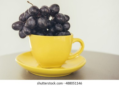 Black grapes in yellow cup
