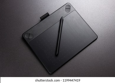 Black graphic tablet and pen. Designer tool for drawing