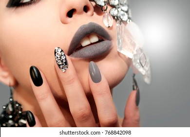 Black gray glam matte makeup and manicure with rhinestones and decoration on the girl's face closeup.