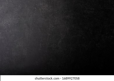 Black gray painted concrete texture or background with shadow and grain elements. High contrast and resolution image with place for text. Template for design