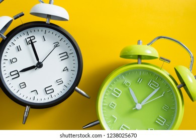 Black and green alarm clocks on yellow color background.