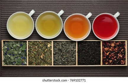 Black , green and fruit tea cups / dry tea leaves assortment in boxes