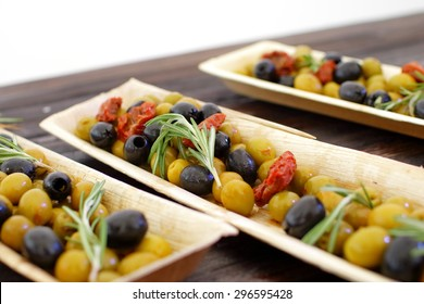 black and green olives, herbs, sun-dried tomatoes in an oblong dish
