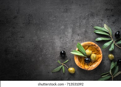 Black and green olives and oil  in wooden bowl on black slate background. Top view  with space for text.