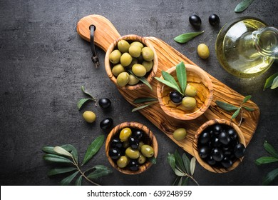 Black and green olives and olive oil bottle. Top view on black background with copy space.