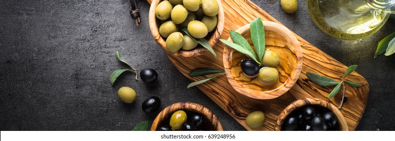 Black and green olives in wooden bowls and olive oil bottle. Top view on black background. Long banner format.