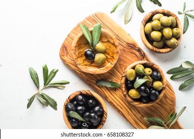 Olives noires et vertes dans des bols en bois et une bouteille d'huile d'olive. Vue de dessus sur fond blanc avec place pour texte.