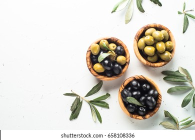 Black and green olives in wooden bowls on white. Top view  with space for text.
