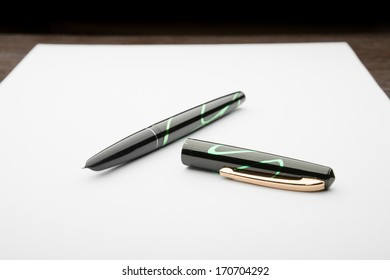 A black and green open fountain pen on a white sheet of paper, on a wooden desk