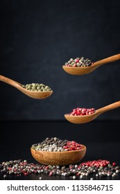 Black, green and pink pepper in a wooden spoon on dark background. Spice pepper peas dry fragrant. Condiments on wooden plate. Seasoning for cooking