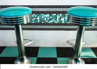 Black and green: tyipical american diner vintage interiors with stools and checkered floor