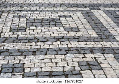Black and grey cobblestones of a footpath have been laid in a geometrical pattern. They are worn with time.