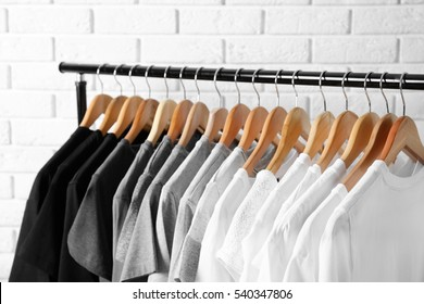 Black, grey and white t-shirts on hangers against brick wall, close up view