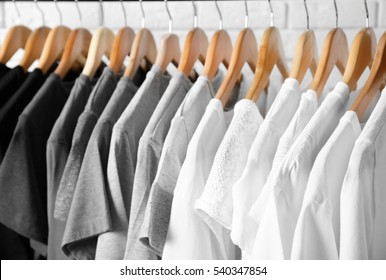 Black, grey and white t-shirts on hangers, close up view