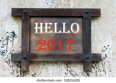 "Black and grey wooden board on wall with words of "" hello 2017"""