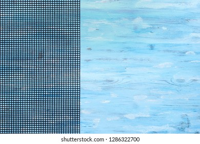 Black grid from left side of turquoise painted old board, retro abstract food background