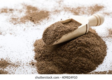 black grinded pepper powder on white table with scoop