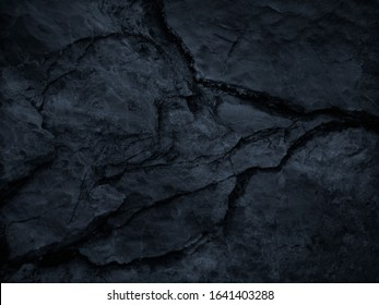 Black grunge background. Dark gray rocky texture with a cracked surface. Close-up. Black rough stone background. Black and white distressed backdrop.