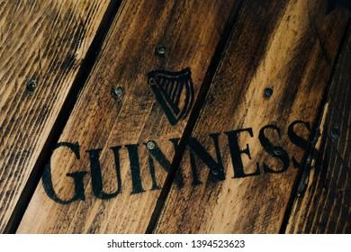 Black Guinness beer logo on rustic weathered wood