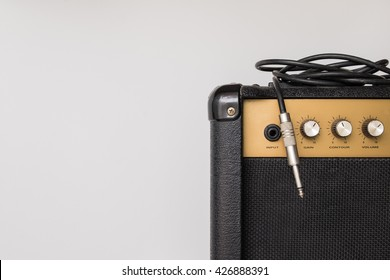 Black guitar amplifier with jack cable on white  background
