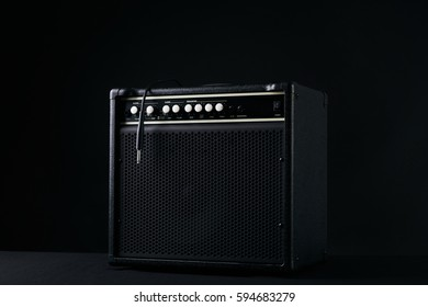 Black guitar amplifier with jack cable on black background.