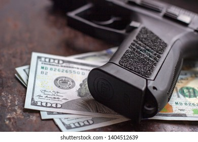 Black gun on American dollars background. Military industry, war, global arms trade, weapon sale, contract killing and crime concept
