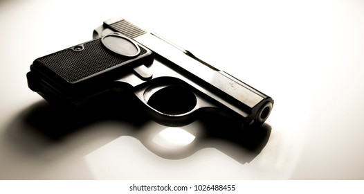 Black gun on white table. Hand Gun.